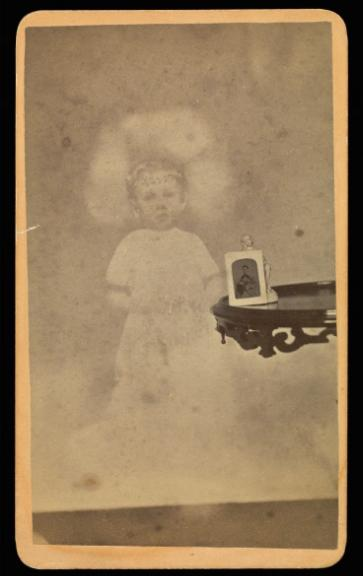 """Child """"spirit"""" with photograph and figurine on table"""